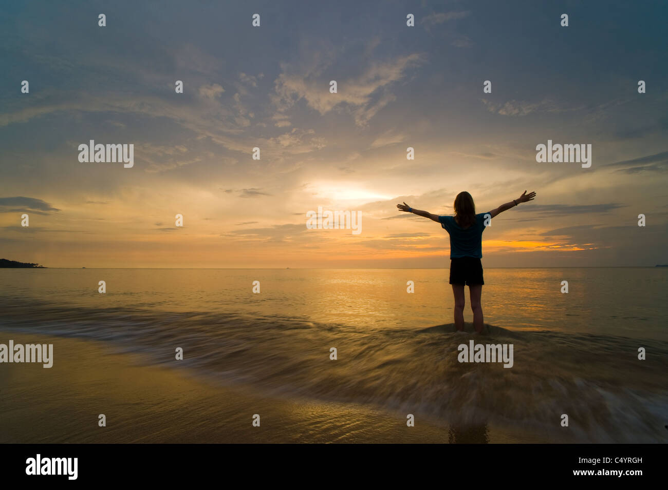 Une jeune femme de la plage, debout dans la mer au coucher du soleil avec ses mains en l'air, la célébration Photo Stock