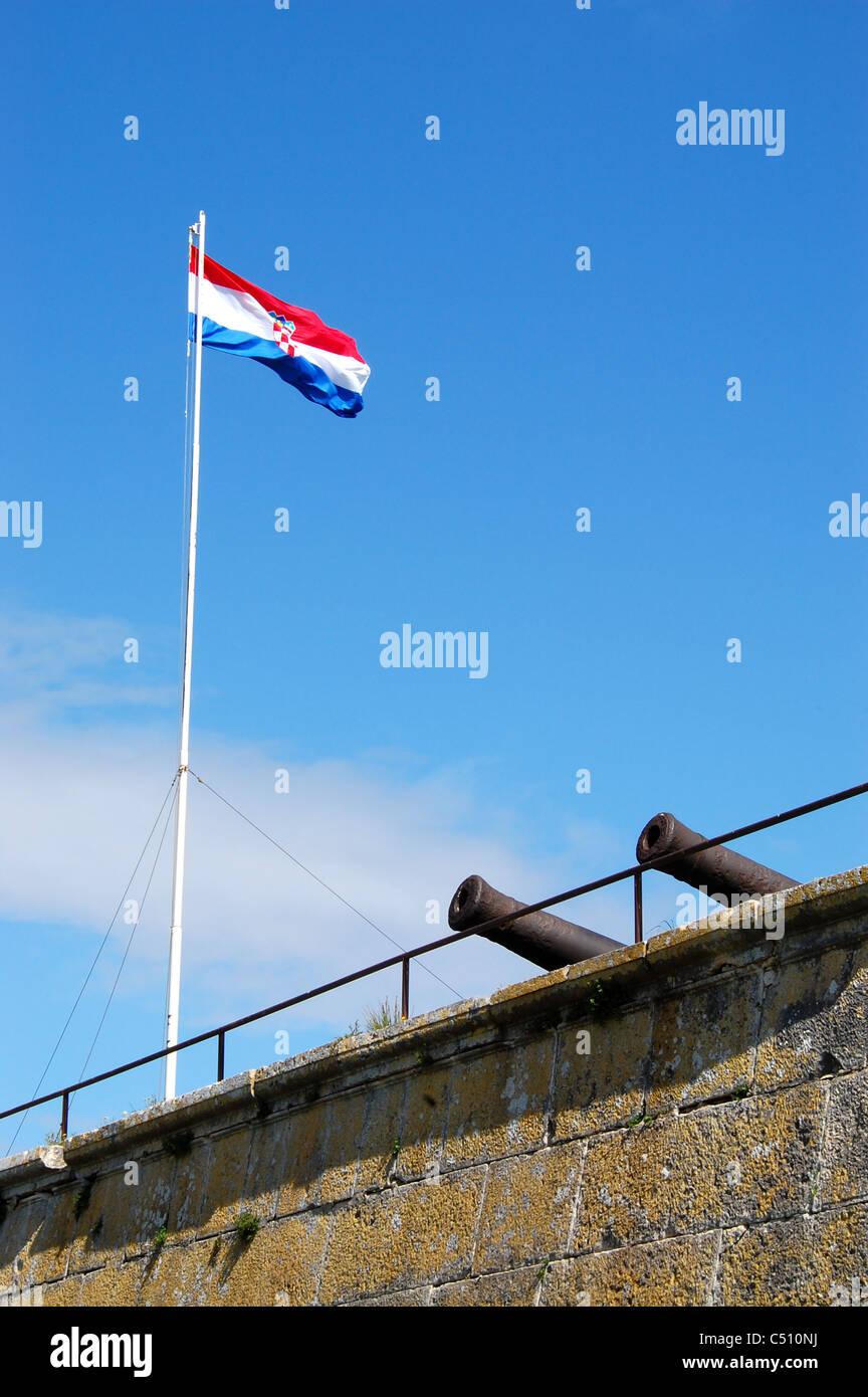 Drapeau croate des volets dans le vent contre le ciel bleu, au-dessus d'un mur avec des canons en saillie. Le Photo Stock