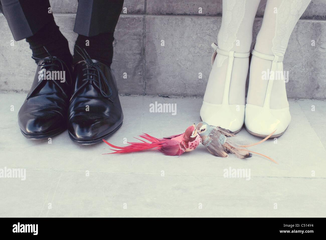 Couple assis côte à côte, les oiseaux d'amour porte-bonheur par leurs pieds, low section Photo Stock
