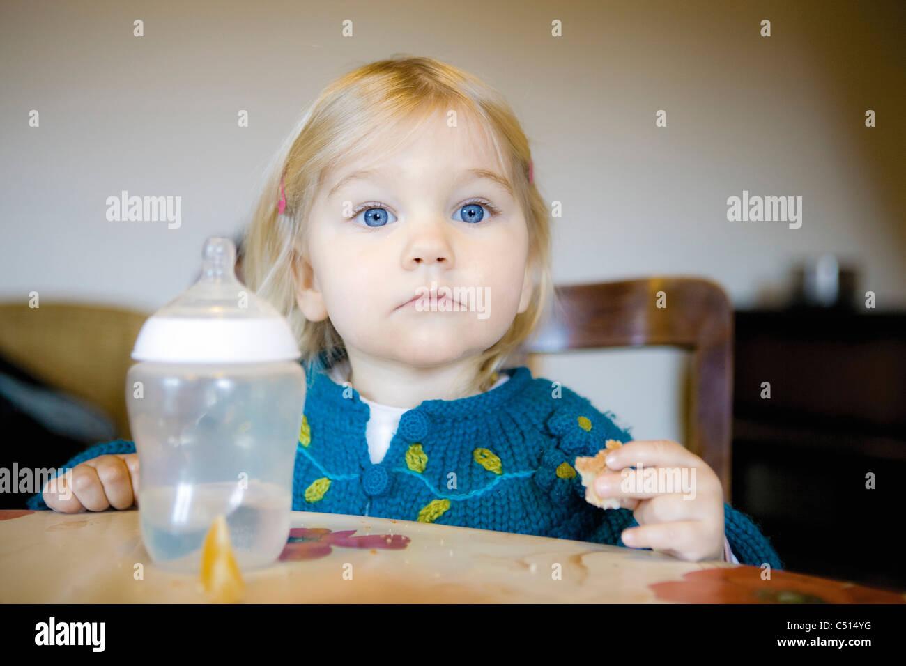 Baby Girl eating snack, portrait Banque D'Images