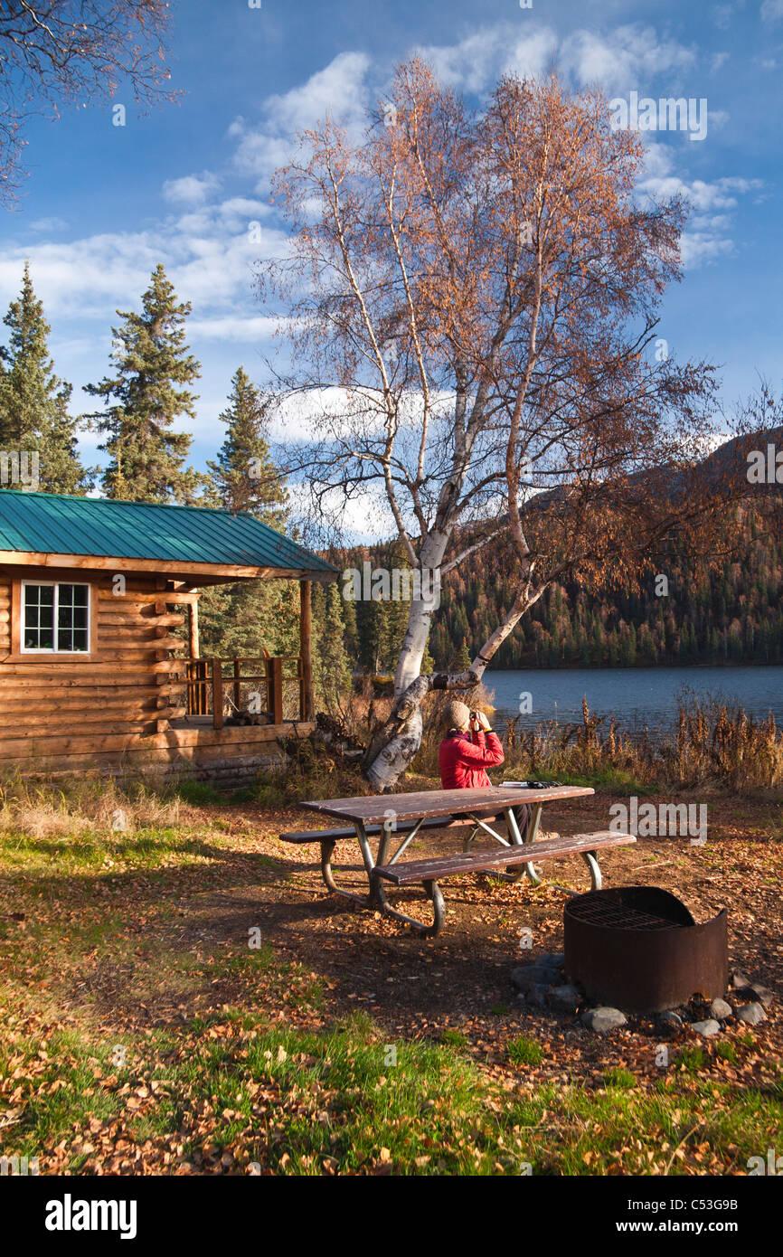 Femme jouit d'une vue sur dans les jumelles alors qu'à une table de pique-nique, Byers Lake Public Photo Stock