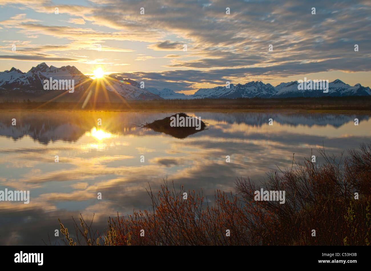 Soleil se lève sur les montagnes Chugach, avec un étang et Beaver Lodge au premier plan, l'Alaska, Photo Stock