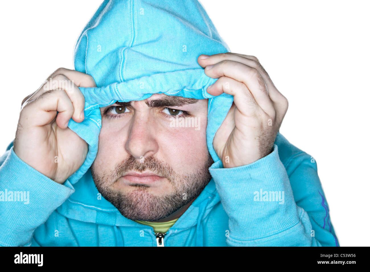 Un homme de race blanche avec une expression interrogateur tire sur sa capuche sur son front. Photo Stock