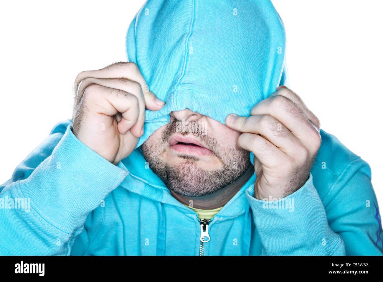 Homme hirsute tirant une capuche bleu vif sur son visage, avec une expression comique. Photo Stock