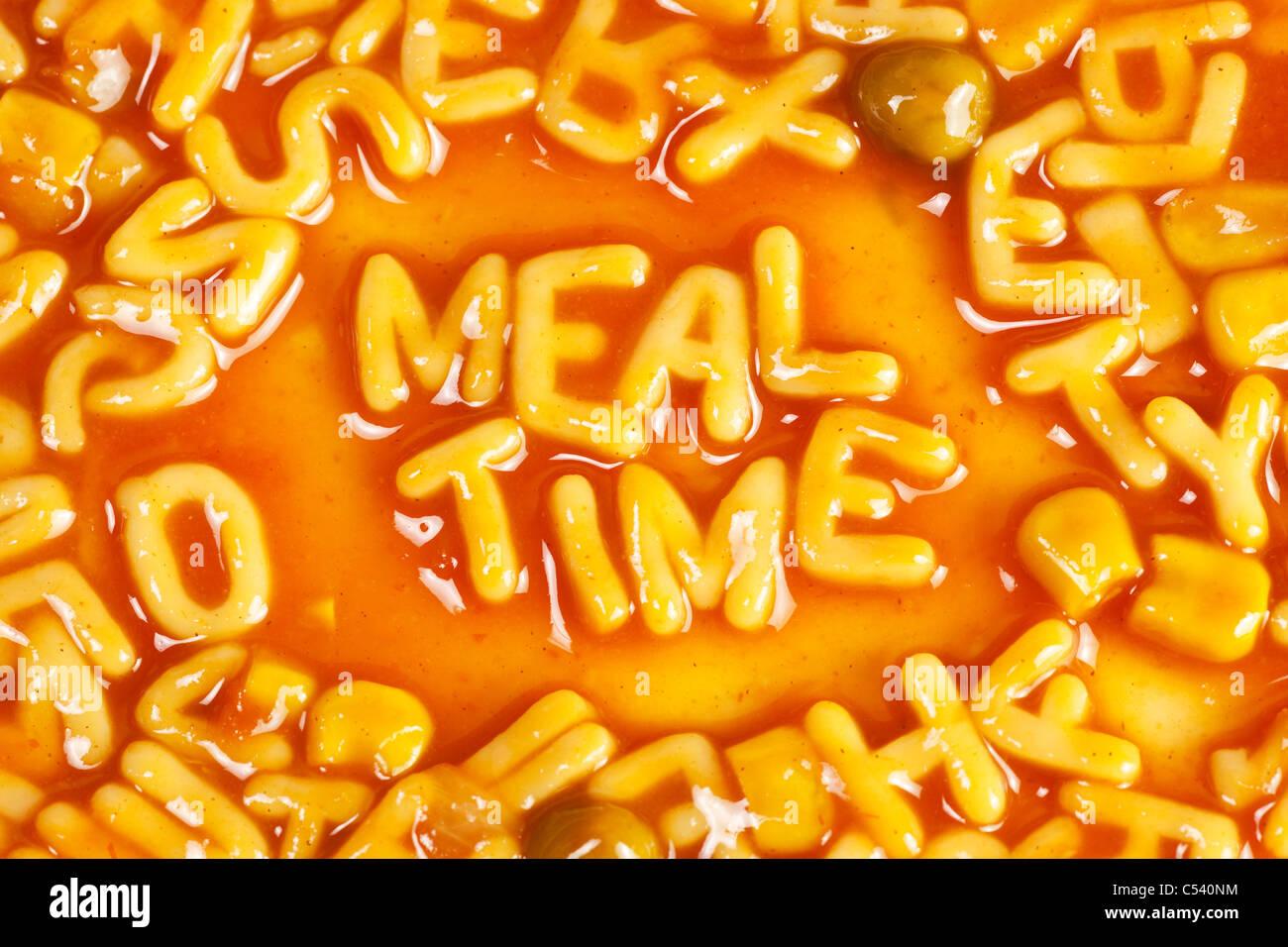 Pâtes en forme Alphabet formant le mot repas en sauce tomate Photo Stock