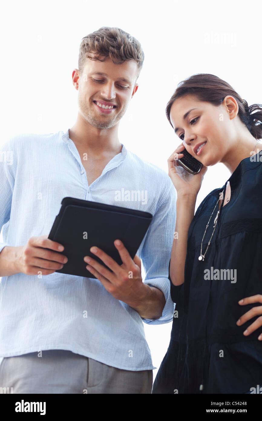 Low angle view of a young couple à l'aide de gadgets électroniques Photo Stock