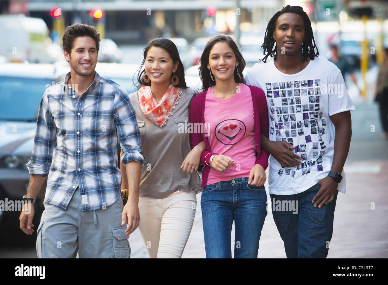 Amis marchant sur la route à des voitures Photo Stock