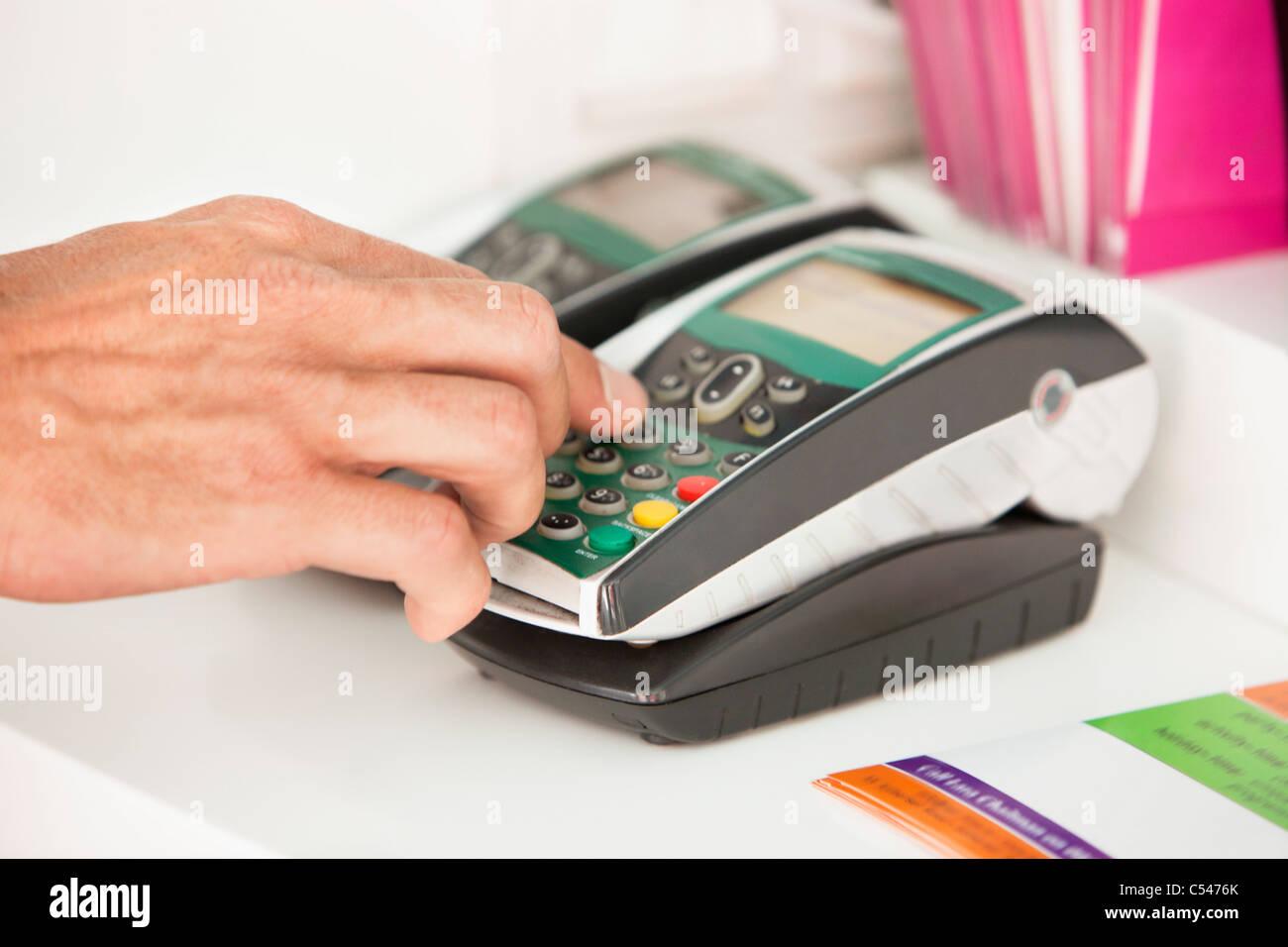 Préposé aux ventes à l'aide d'un lecteur de carte de crédit au comptoir Photo Stock