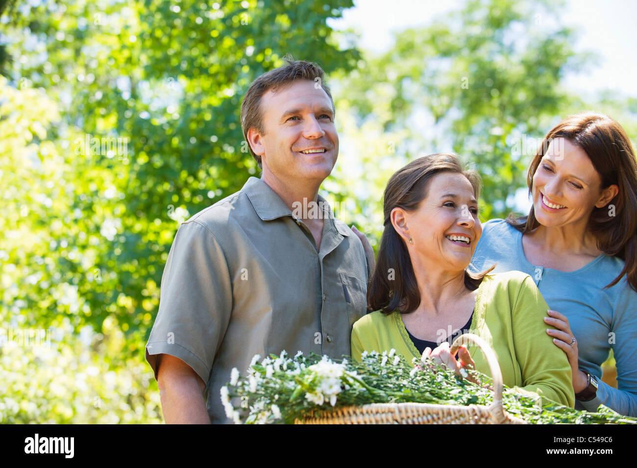 Femme debout avec son fils et sa belle-fille en maintenant panier de fleurs Photo Stock