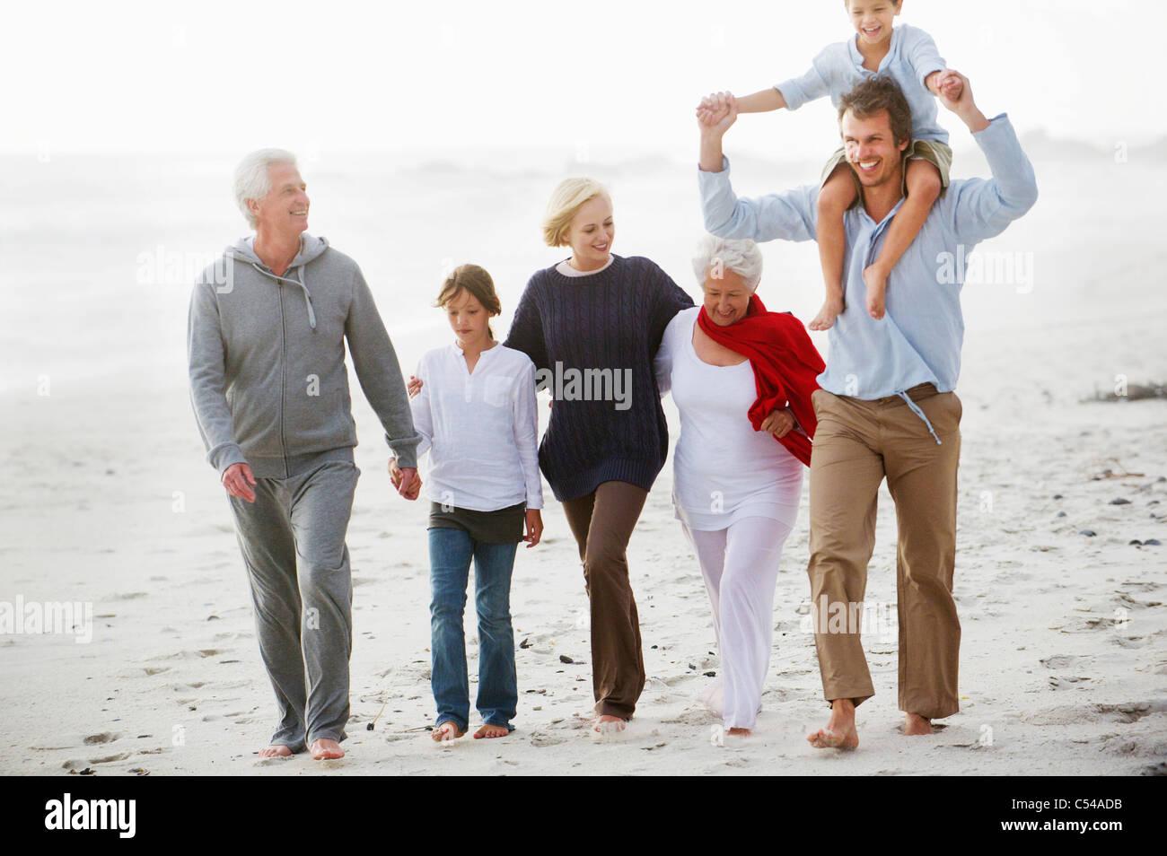 Multi-generation family walking on the beach Photo Stock