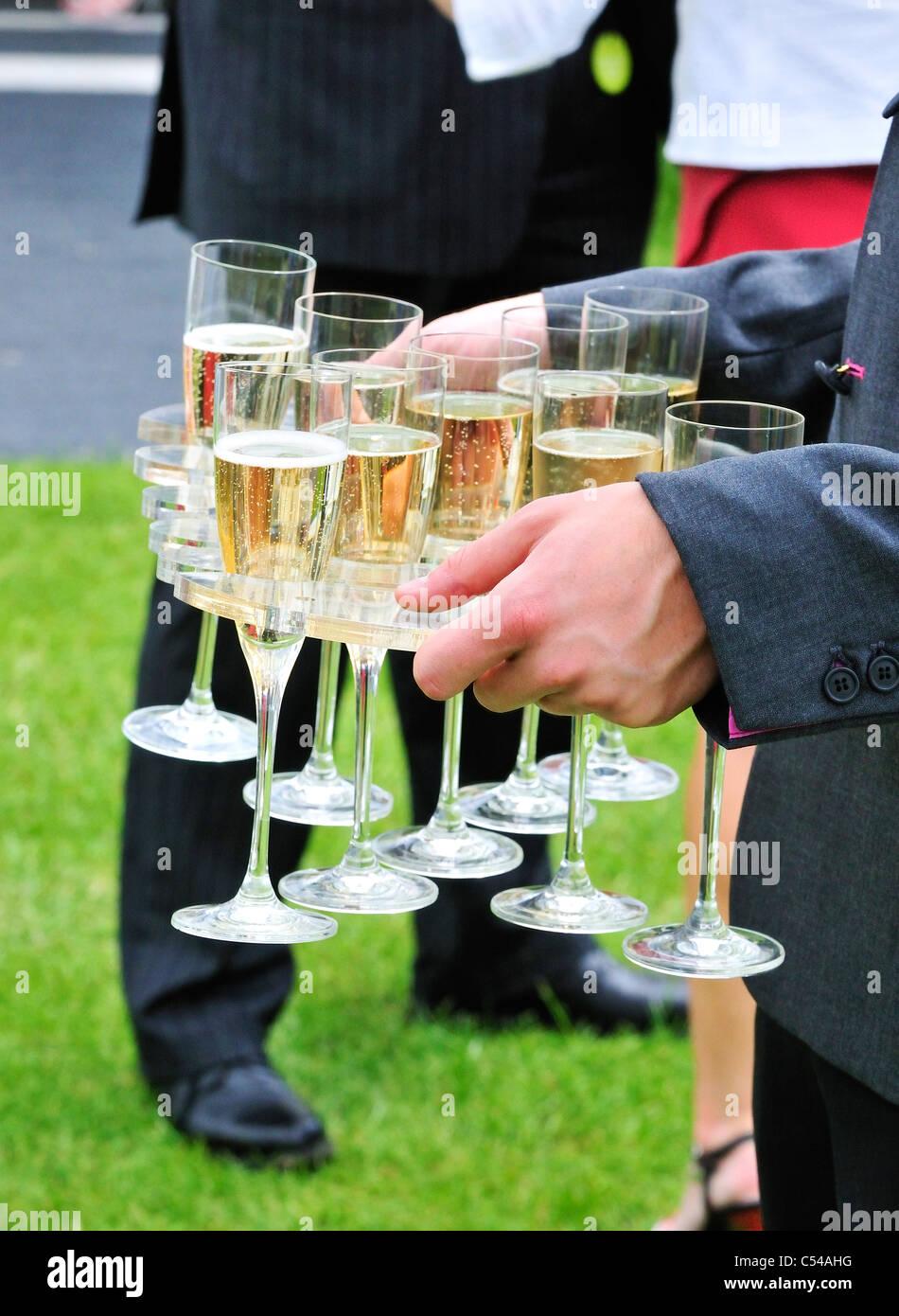 Homme portant des verres de champagne dans une zone de tentes hospitalité sponsors au Henley Royal Regatta, Henley Banque D'Images