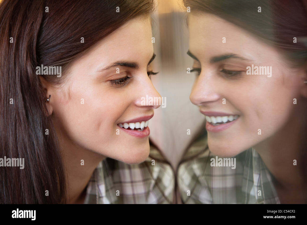 Smiling woman looking at son propre reflet dans le miroir Photo Stock