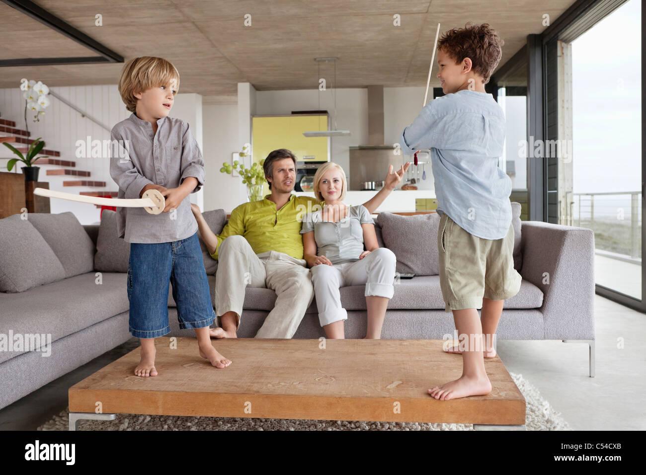 Garçons jouant avec leurs parents assis sur un canapé Banque D'Images