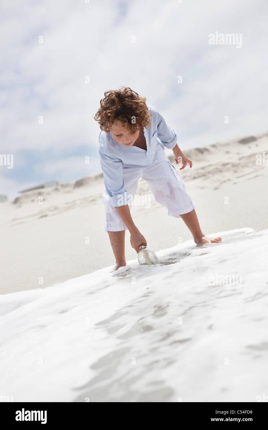 Boy putting bouteille avec message dans de l'eau sur plage Photo Stock