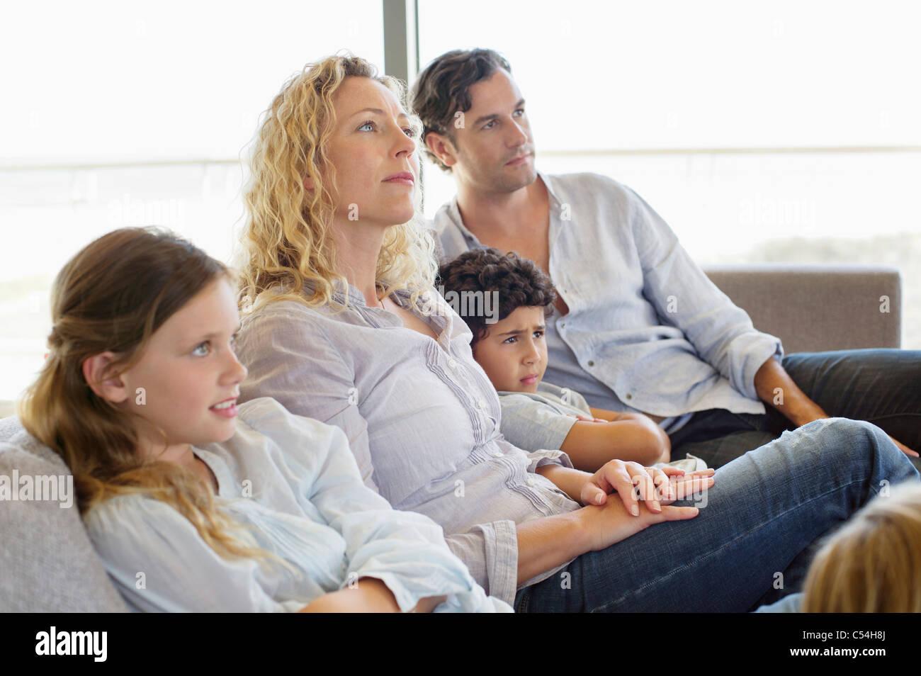 Famille avec trois enfants assis sur un canapé Banque D'Images