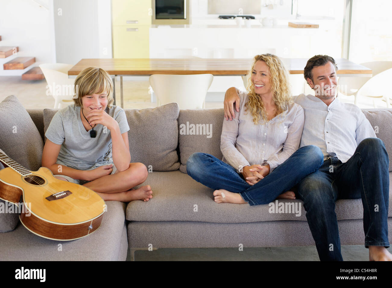 Family sitting on a couch and smiling Banque D'Images