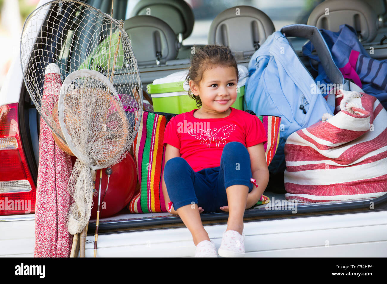 Cute little girl sitting in car trunk Banque D'Images