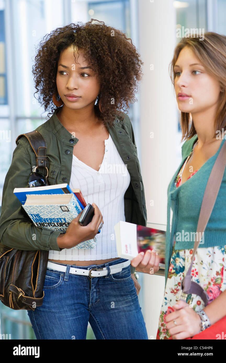 Deux femmes à la voiture tandis que holding books Photo Stock