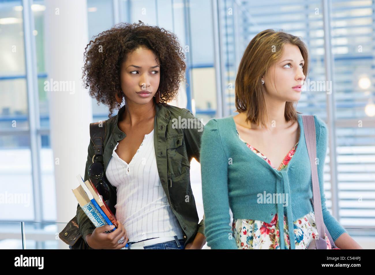 Deux femmes à la recherche de là avec des livres dans la main à l'université Photo Stock