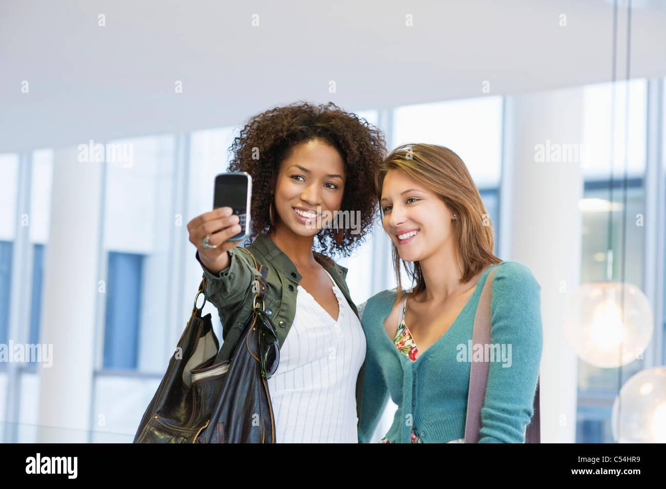 Deux femmes prenant des photos d'eux-mêmes Photo Stock