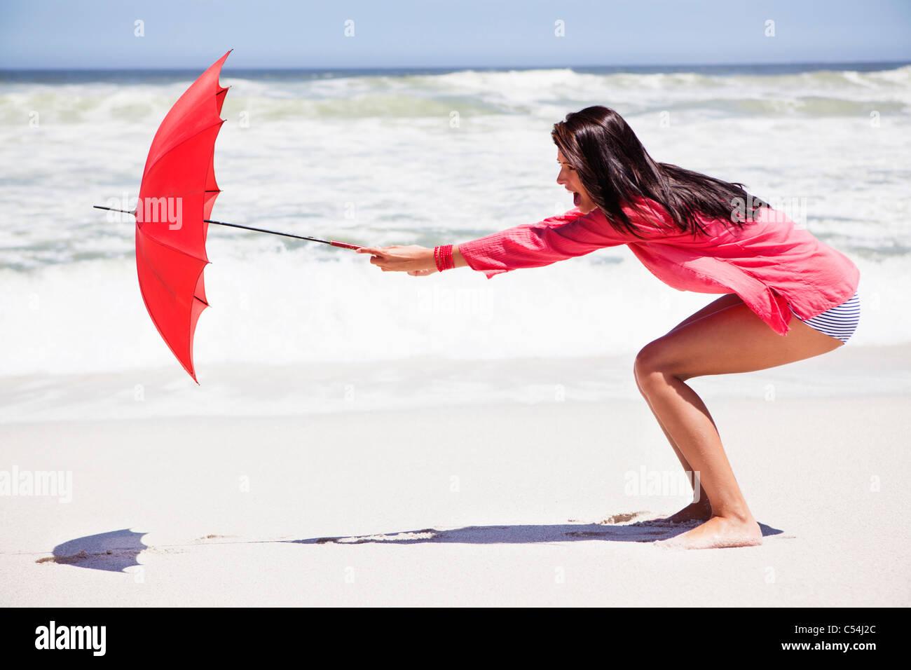 Femme essayant de tenir un parapluie dans le vent fort sur la plage Banque D'Images