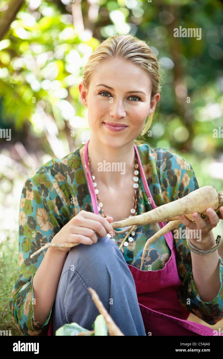 Smiling woman holding radish Photo Stock