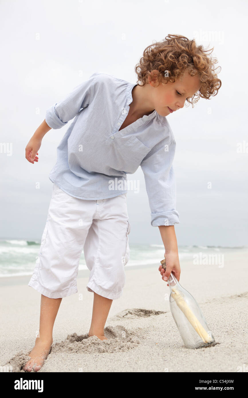 Boy Reaching for message in a bottle on beach Banque D'Images