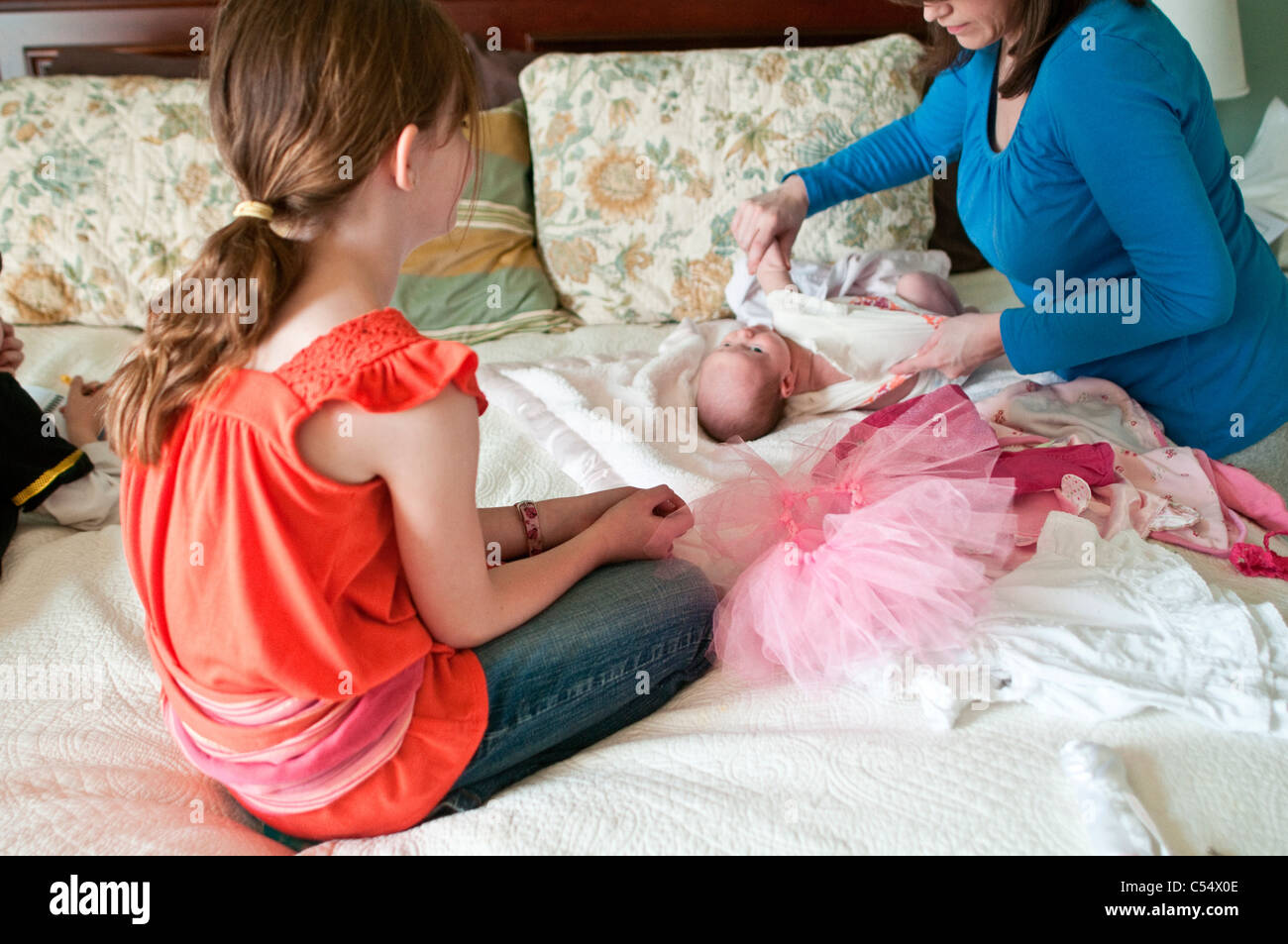 Aider fille mère dressing up baby girl on bed Banque D'Images
