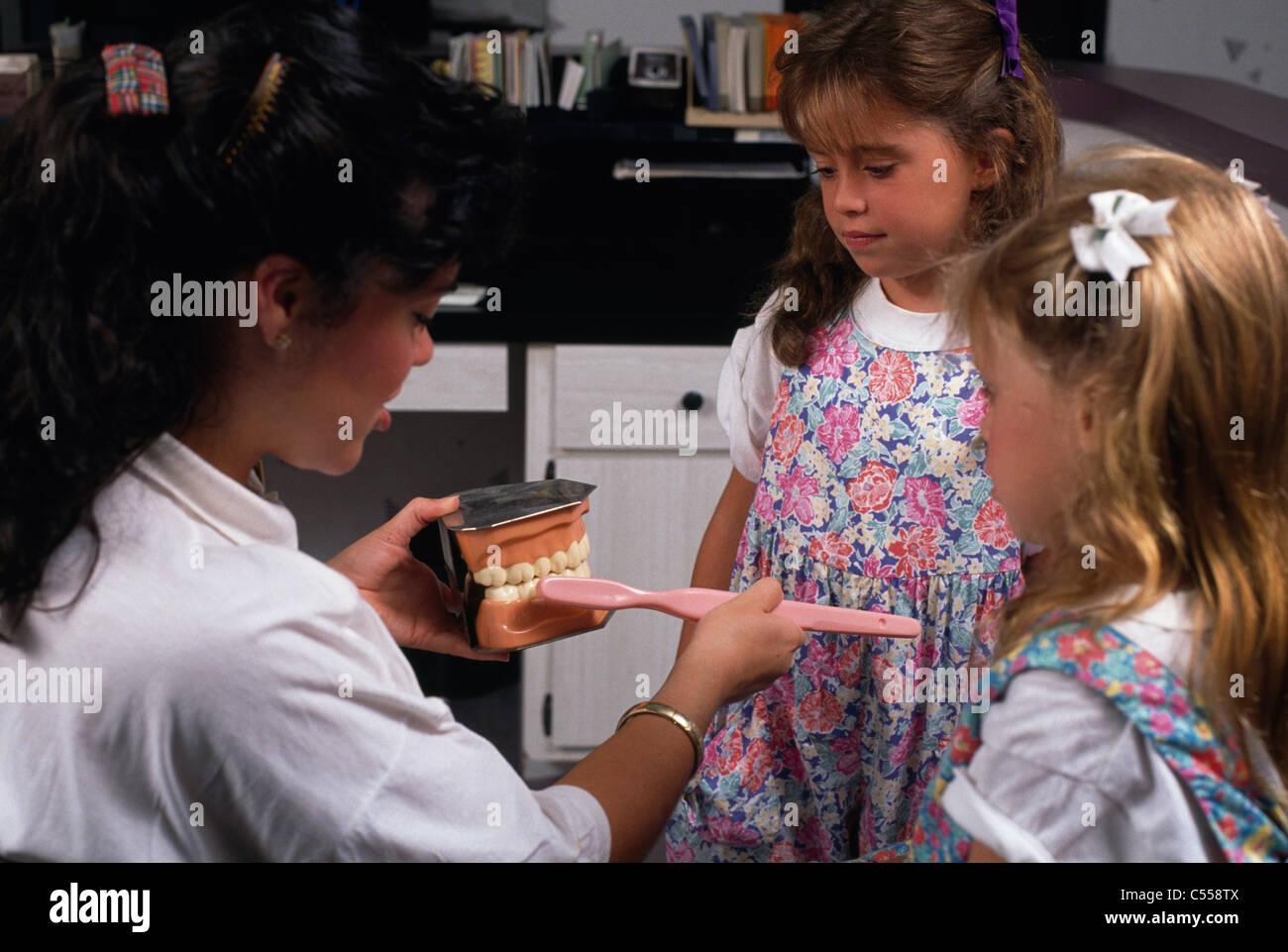Femme dentiste démontrant l'utilisation de prothèses sur la brosse à dents en face de deux jeunes filles Banque D'Images