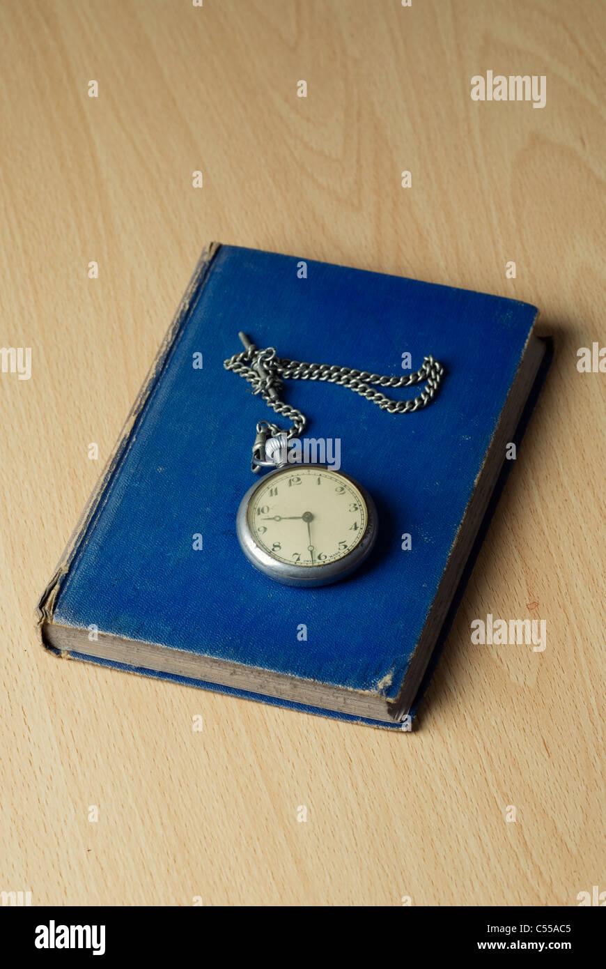 Montre de poche antique au-dessus d'un livre bleu Photo Stock