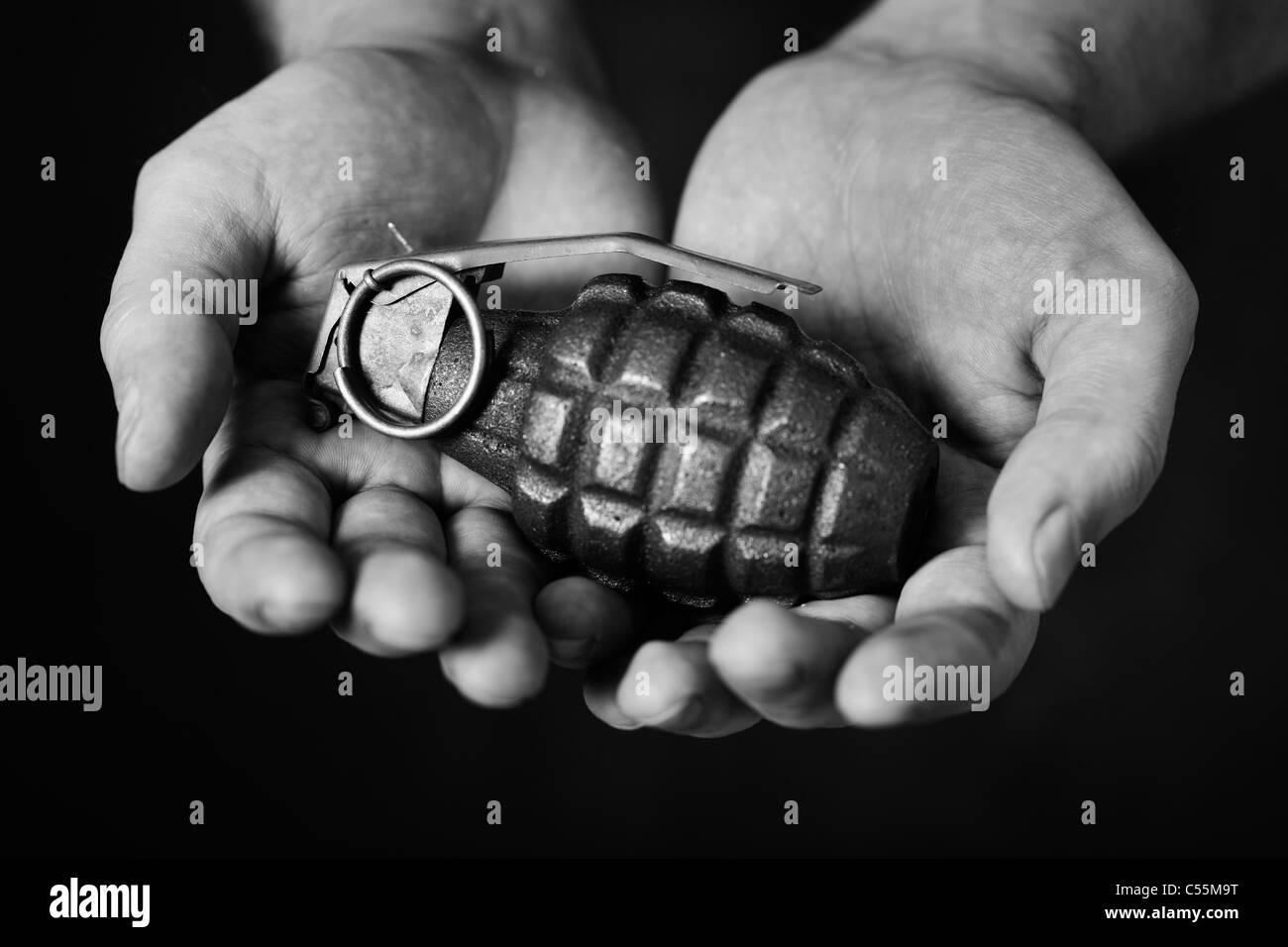 Homme tenant une vieille grenade à main dans ses mains Banque D'Images