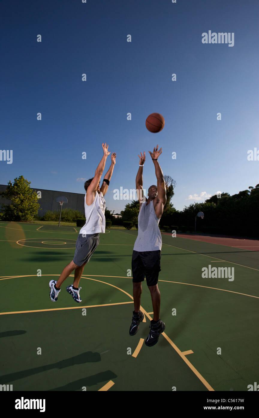 Jump shot pendant deux sur deux match de basket-ball d'être défendu Photo Stock