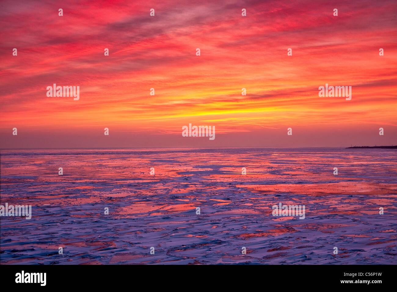 Les Pays-Bas, Oosterdijk, hiver, neige, vue sur lac gelé appelé IJsselmeer. Le lever du soleil. Photo Stock