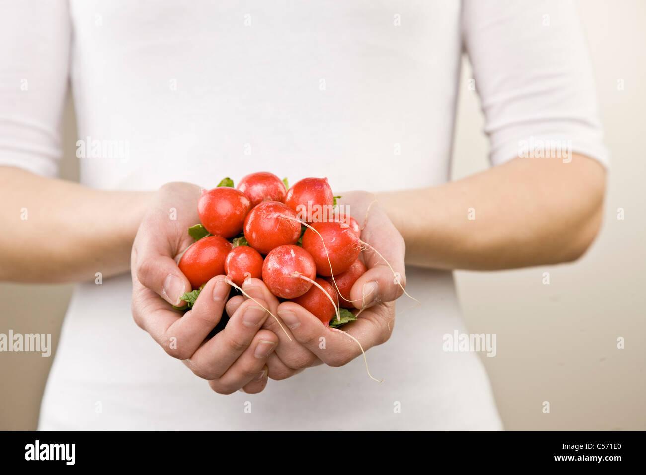 Femme avec poignée de radis Photo Stock