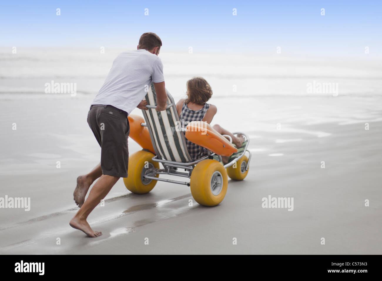 Man pushing petite amie dans le panier on beach Banque D'Images