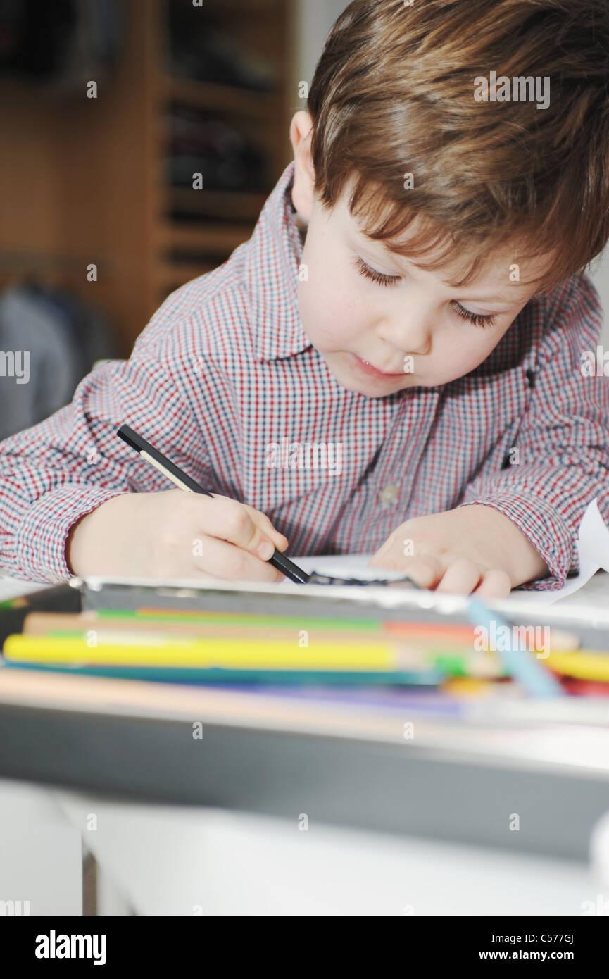 Garçon dessin avec crayons de couleur Photo Stock