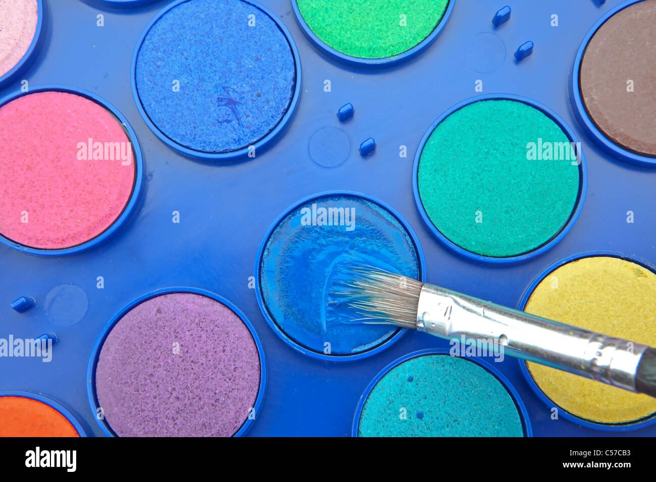 Les couleurs de l'eau dans une boîte de peinture avec pinceau Photo Stock