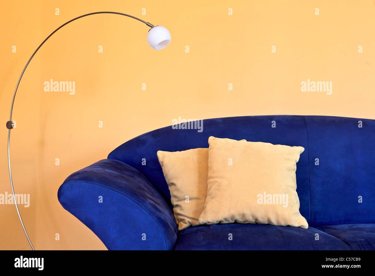 Un canapé bleu avec une lampe de lecture et des oreillers et des murs jaune Photo Stock