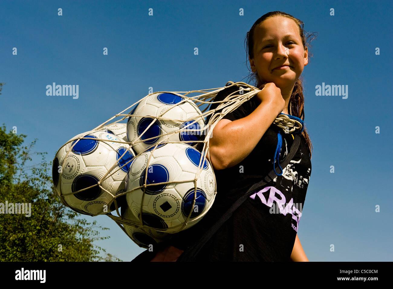 Low angle view of a smiling girl avec ballons dans un sac filet contre ciel bleu clair Banque D'Images