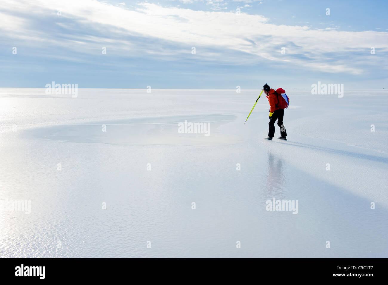 Vue latérale d'un patineur sur glace d'un lac paisible contre ciel nuageux Photo Stock
