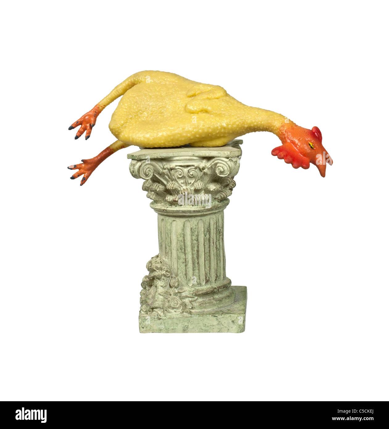 Blague classique illustré par un poulet en caoutchouc sur un piédestal en pierre formelle - chemin inclus Photo Stock