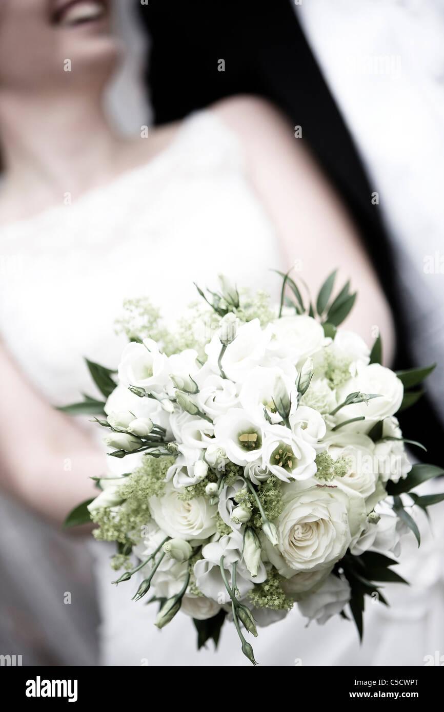 Close-up midsection of a bride holding a bouquet Banque D'Images
