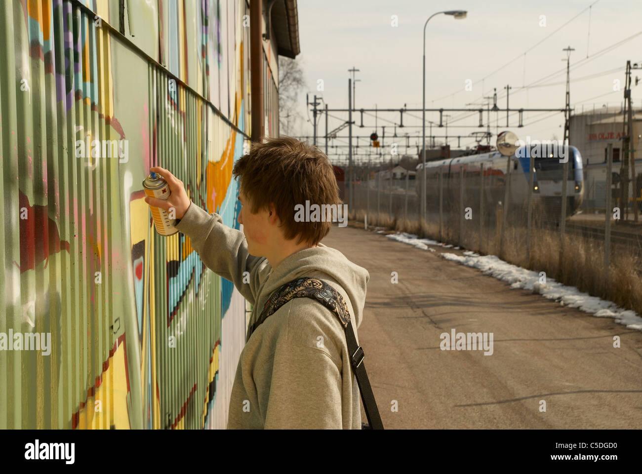 Vue latérale d'un adolescent sur le mur de graffiti de pulvérisation Banque D'Images