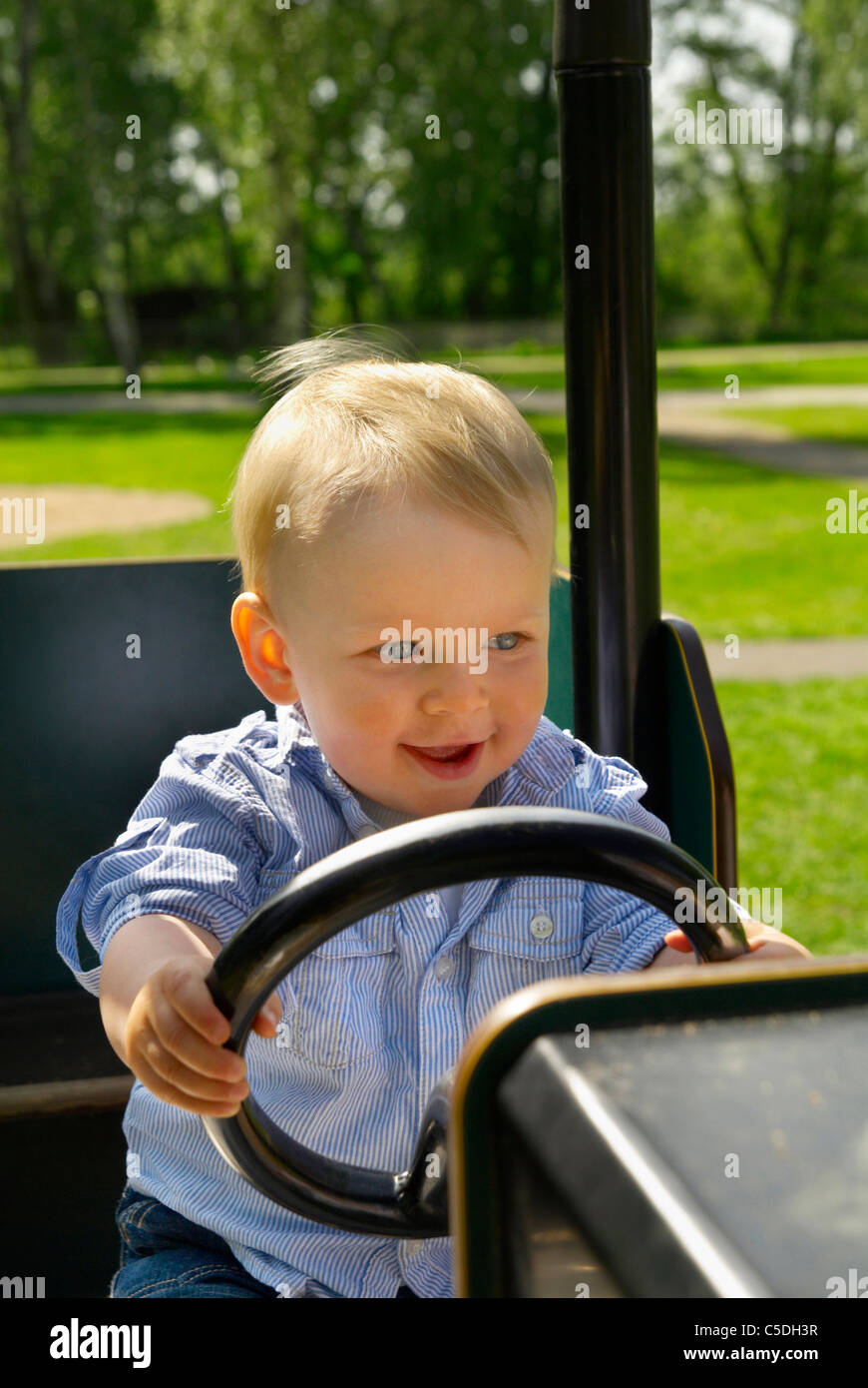 Cute little boy driving cropped petite voiture dans l'aire de jeux Photo Stock