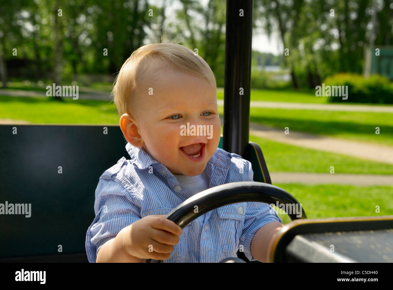 Happy little boy driving cropped petite voiture dans l'aire de jeux Photo Stock