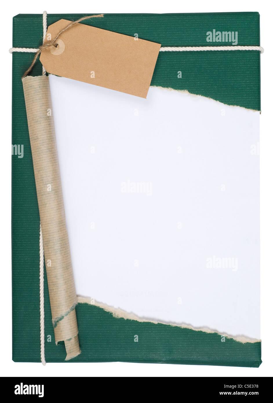 Close-up d'un cadeau emballé avec du papier d'emballage vert déchiré contre fond blanc Photo Stock