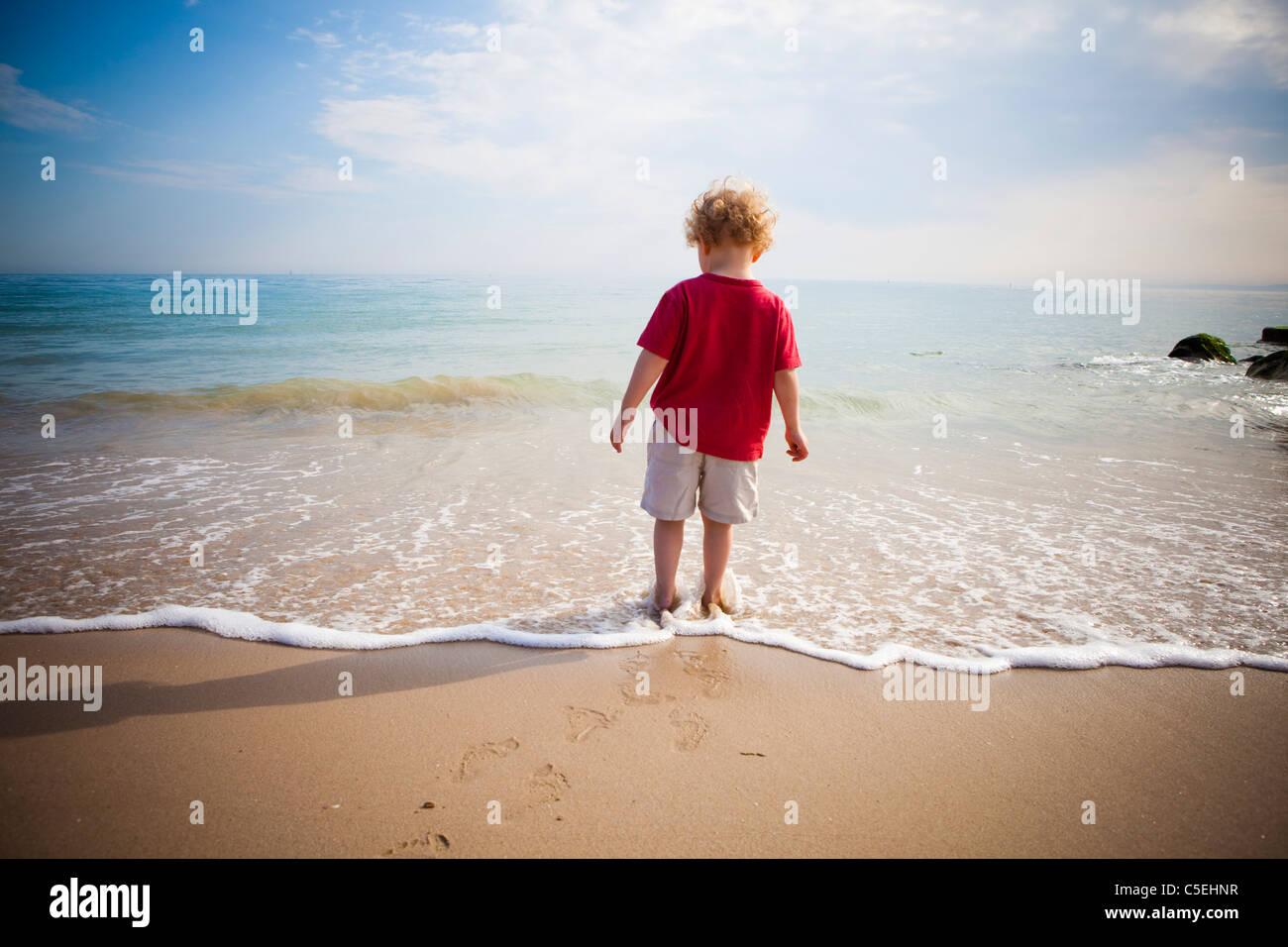 Garçon debout dans la mer Photo Stock