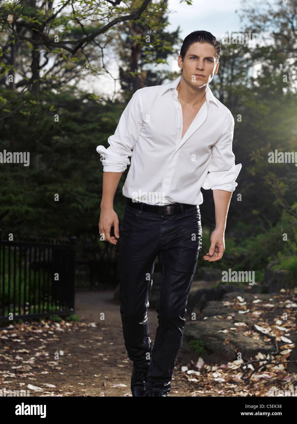 Photo d'un élégant jeune homme marcher dans un parc dans la soirée Photo Stock