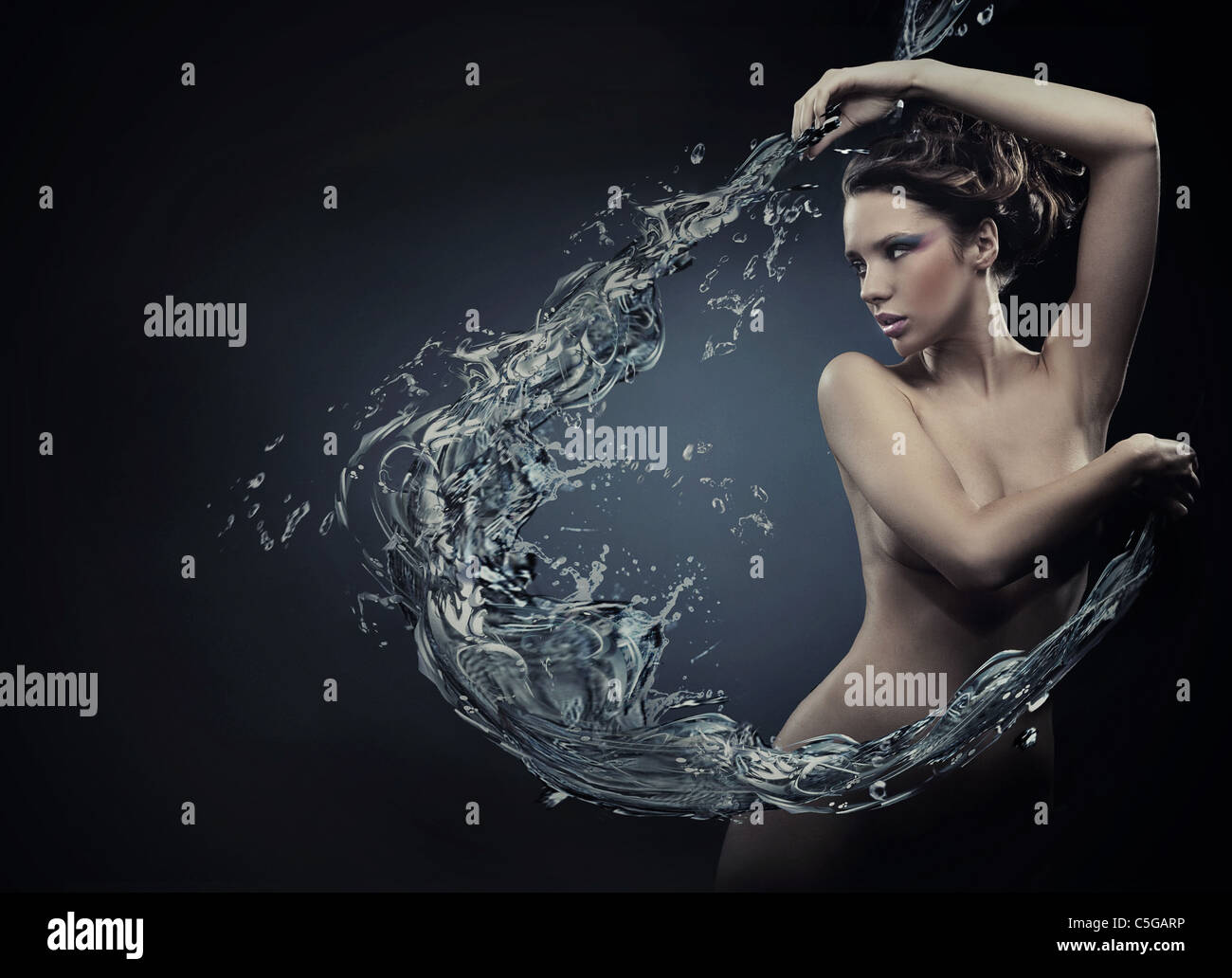 Jeune beauté danse avec les éclaboussures d'eau Photo Stock