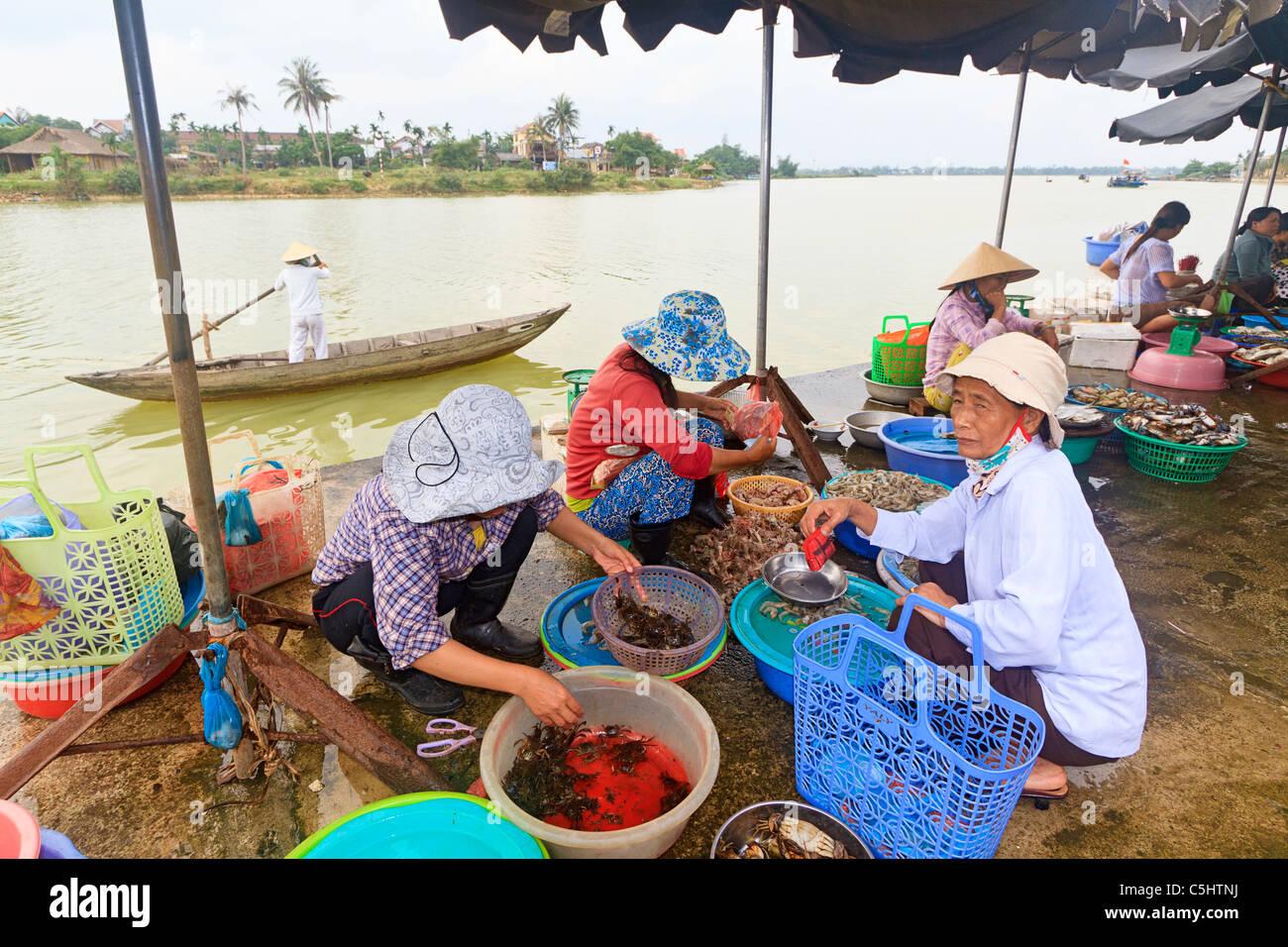 Les femmes vendent les crevettes et crabes au cours du marché le long de la rivière Thu Bon à Hoi Photo Stock